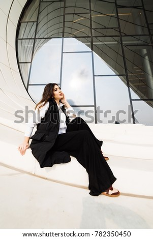 stylish attractive woman in black suit posing against the background of an unusual building in the city of Baku