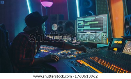 Stylish Audio Engineer / Producer Working in Music Record Studio. Computer Screen Showing User Interface of Digital Audio Workstation Software with Track Song Playing. Uses Control Desk to Create Song