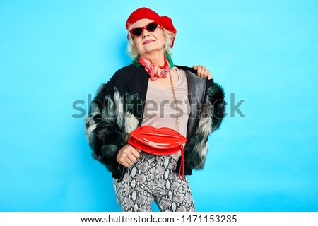 stylish awesome cool old woman in red hat and trendy coat posing to the camera. isolated blue background. studio shot.autumn, fall, spring clothes . stylish clothes for any age