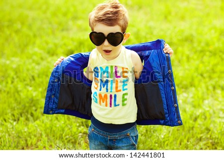 Stylish baby boy with ginger hair in trendy sunglasses (heart form) & blue jacket standing in the park and singing a song. Hipster style. Sunny weather. SMILE word printed o t-shirt. Outdoor shot