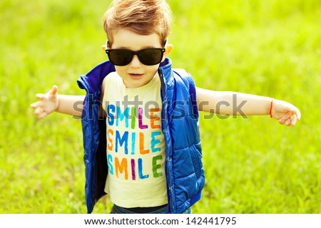 Stylish baby boy with ginger (red) hair in trendy sunglasses and blue jacket standing in the park & trying to hug somebody. Hipster style. Sunny weather. SMILE word printed on t-shirt. Outdoor shot