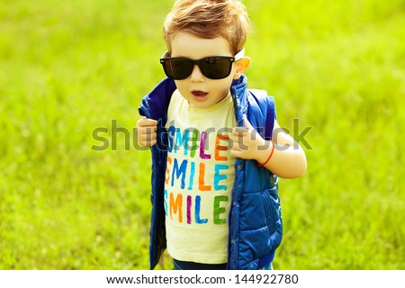 Stylish baby boy with ginger (red) hair in trendy sunglasses and blue jacket standing in the park. Hipster style. Sunny weather. SMILE word printed on t-shirt. Copy-space. Outdoor shot