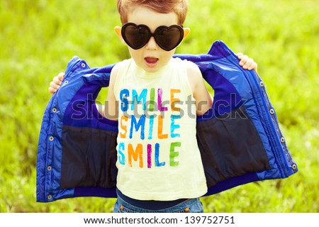 Stylish baby boy with ginger (red) hair in trendy sunglasses (heart form) and blue jacket standing in the park and singing a song. Hipster style. Sunny weather. Outdoor shot