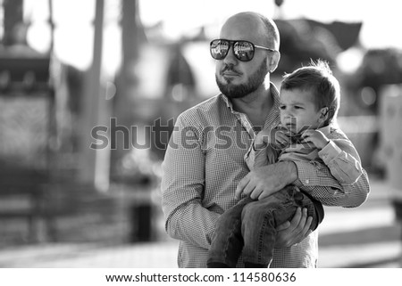 stylish baby boywith stylish father  having fun outside in the amusement Park in sunglasses,black and white