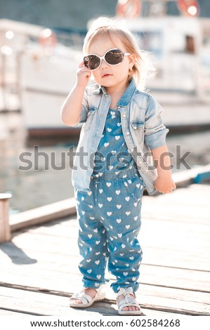 Stylish baby girl 2-3 year old wearing denim clothes outdoors. Looking at camera. Summer time.  #602584268