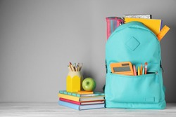 Stylish backpack with different school stationery on table against light grey background. Space for text