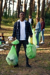 Stylish bearded black man with full rubbish packs on background of his friends activists picking up rubbish at forest.