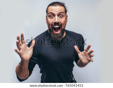 Stylish bearded hipster man with appealing dark eyes smiling into camera. Hipster man with beard  having cheerful look. Positive emotions.Crazy emotions. joy. The emotional portrait.  #765041452