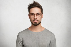 Stylish bearded male student wears round spectacles, has trendy hairstyle, looks confidently, thinks about coming session, isolated over white concrete background. People and human expressions