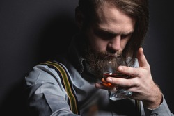 Stylish bearded man in a shirt with suspenders sniffs a glass sniffs of whiskey. studio portrait