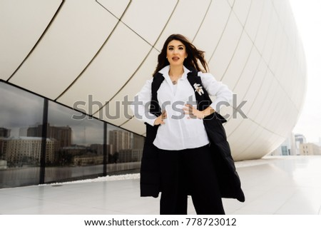 stylish beautiful brunette girl in black suit posing against the background of an unusual building in Baku