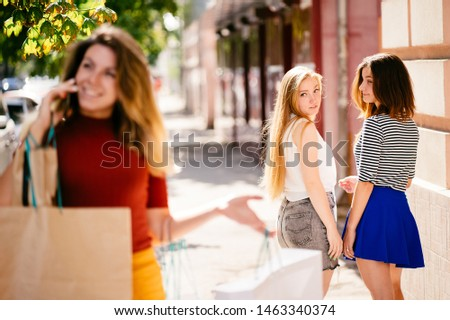Stylish beautiful confident woman with many shopping bags in hands walking in the street. Envy, self-confidence concept