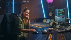 Stylish, Beautiful Female Audio Engineer Working in Music Recording Studio, Uses Mixing Board Create Song. Looking at Camera Portrait of a Girl Artist Musician Working at Control Desk and Smiling