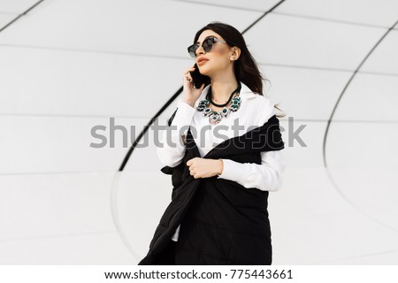 stylish beautiful girl in a black suit and sunglasses talking on the phone, traveling, walking through Baku