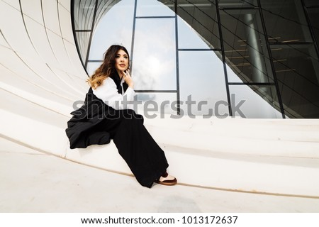 stylish beautiful girl in a black suit posing against the background of the unusual architecture of the city of Baku