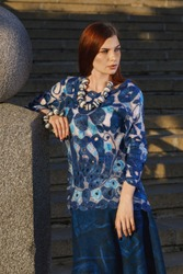 Stylish beautiful girl in designer clothes. She wore a tunic, blue lace. Picture is made on motives of Russian porcelain painting - Gzhel, close-up