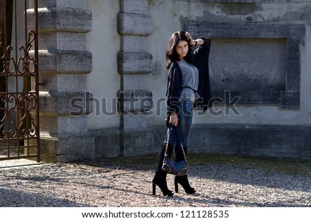 Stylish beautiful girl is posing in the courtyard  of the old castle  under bright sunbeams. Tuscan, Italy
