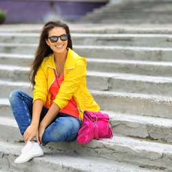 Stylish beautiful girl sitting on a stairs in colorful clothes