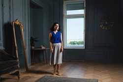 Stylish beautiful longhaired woman a blue shirt and skirt in glasses standing in a room in modern appartment interior. Lady and looking aside and smiling. The wind blows through the girls hair