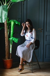 Stylish beautiful longhaired woman a white shirt and skirt sitting on chair by palm tree in pot in appartment interior. Young girl in glasses, posing and looking at camera