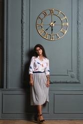 Stylish beautiful longhaired woman a white shirt and skirt standing by wall with a clock in appartment interior. Young girl in glasses leaning by wall, posing and looking at camera.