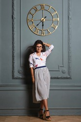 Stylish beautiful longhaired woman a white shirt and skirt standing by wall with a clock in appartment interior. Young girl in glasses leaning by wall, posing and looking at camera