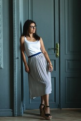 Stylish beautiful longhaired woman in white t-shirt and skirt standing in modern appartment interior. Young girl leaning by doors in glasses looking aside.