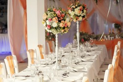 Stylish beautiful luxury wedding decor with a lot of flowers on the tables in restaurant hall