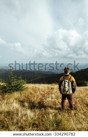 stylish beautiful traveling man hiking in the mountains on a background of a forest #334290782