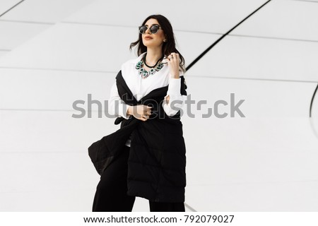 stylish beautiful woman in black suit and sunglasses posing in the city of Baku