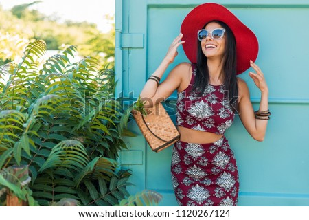 Stock Photo stylish beautiful woman in red hat posing on blue background, printed outfit, summer style, fashion trend, top, skirt, skinny, straw handbag, sunglasses, accessories, smiling, happy, tropical vacation