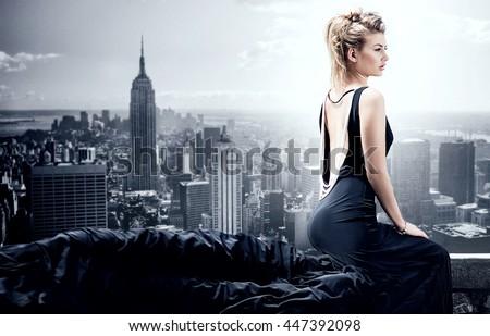 Stylish beautiful woman posing in black elegant dress. Skyline on background.