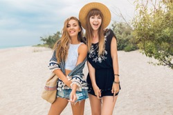 stylish beautiful women on summer vacation on tropical beach, bohemian style, friends together, fashion accessories, smiling, happy emotion, positive mood, shorts, straw hat, having fun