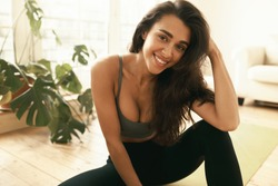 Stylish beautiful young Arabic woman in active wear relaxing at home, sitting on floor after intensive workout, training muscles and burning calories. Weight loss and body shape concept