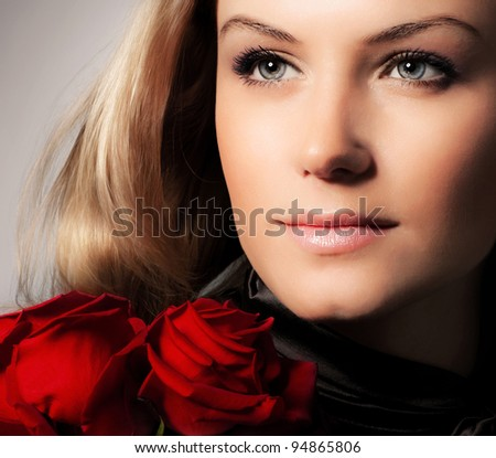 Stylish beautiful young woman holding red roses bouquet, closeup on gorgeous face, tender flowers, blond female over dark background, Caucasian model girl with fresh plant, lady in love concept