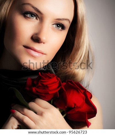 Stylish beautiful young woman holding red roses bouquet, tender flowers in hands, blond female over dark background, gorgeous girl with fresh plant, lady in love concept
