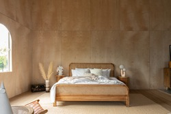 Stylish Bedroom corner with rattan headboard and bed with soft pillows setting with white pillows plywood wall on the background / cozy interior design / modern interior