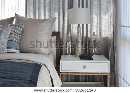 stylish bedroom interior design with striped pillows on bed and decorative table lamp. #302661143
