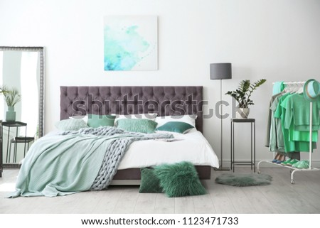 Stylish bedroom interior with clothes rack and mint decor elements #1123471733