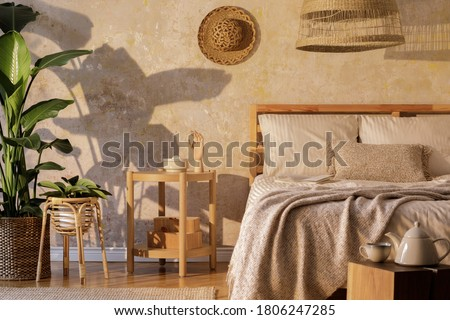 Stylish bedroom interior with design coffee table, furniture, tropical plant, rattan decoration and elegant personal accessories. Beautiful beige bed sheets, blanket and pillows. Template.