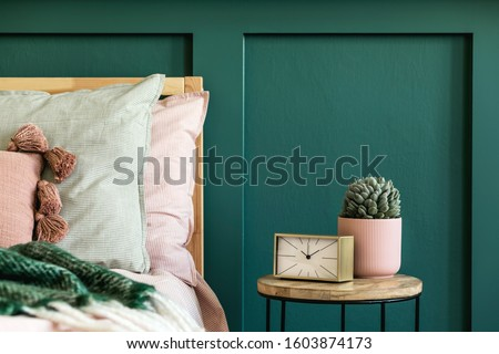 Stylish bedroom interior with design coffee table, plant, gold clock and elegant personal accessories. Beautiful bed sheets, blanket and pillows. Template. Modern home staging. Wall panelling. Details