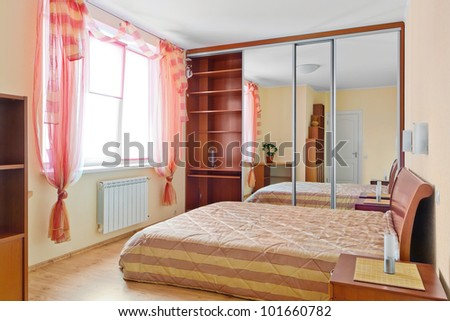 Stylish bedroom interior with double bed in yellow and beige colors - stock photo