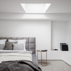 Stylish bedroom white walls, ceiling window and big, gray bed with quilted bed