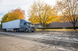 Stylish big rig gray semi truck with grille guard and dry van semi trailer with spoiler skirt on the bottom standing on the autumn road with yellow trees at industrial area waiting for unloading