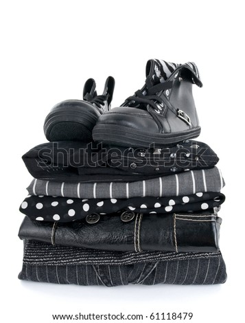 Stylish black clothing and a pair of boots on white background.