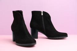 Stylish black female boots on pink background