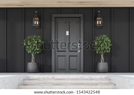 Stylish black front door of modern house with black walls, door mat, trees in pots, stairs and lamps. 3d rendering