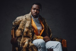 Stylish black hipster with fur sitting on chair