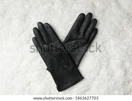 Stylish black leather gloves on artificial snow, top view Stock photo ©