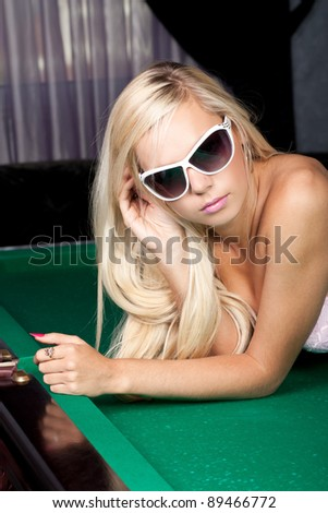 Stylish blond woman in pink lingerie on a pool table